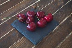 Kirschen auf Schiefer auf Holzabschluß oben Stockfotografie