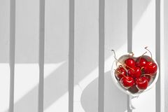 Kirschen Chile im Herz-förmigen Becher auf Holz Lizenzfreie Stockbilder