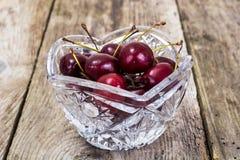 Kirschen in Crystal Bowl auf rustikalem Hintergrund Lizenzfreie Stockbilder