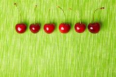 Kirschen in einer Reihe Stockbild