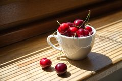 Kirschen in einer weißen Schale auf einem hölzernen Hintergrund Stockbilder