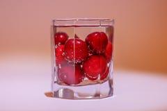 Kirschen im Glas Wasser mit Luftblasen Stockbilder