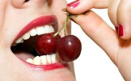 Kirschen zwischen den Zähnen Lizenzfreies Stockbild