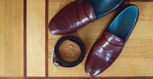 Kirschmänner ` s Schuhe, Gurt und Eheringe in einem Kasten Bräutigam ` s Zubehör am Hochzeitstag Stockfoto