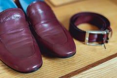 Kirschmänner ` s Schuhe, Gurt und Eheringe in einem Kasten Bräutigam ` s Zubehör am Hochzeitstag Lizenzfreie Stockfotografie