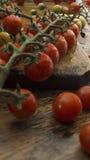 Kirschtomaten auf hölzernem hackendem Brett und Tabelle Lizenzfreies Stockfoto