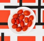 Kirschtomaten auf weißer Platte und rotem geometrischem modernem backgrou Stockfotos