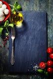 Kirschtomaten, Basilikumblätter, Mozzarellakäse und Olivenöl Stockbilder