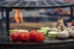 Kirschtomaten, Champignon vermehrt sich, die Zucchini explosionsartig, die auf einer heißen Grilloberfläche gekocht wird Lizenzfreies Stockfoto