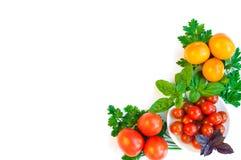 Kirschtomaten, gelbe und rote Tomaten und Grüns auf einer Platte I stockbilder