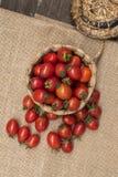 Kirschtomaten, ist- kleine Tomaten auf hölzerner Spitze und Korbgeflecht lizenzfreies stockbild