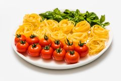 Kirschtomaten, Spaghettis und frischer Basilikum auf einer Servierplatte auf einem weißen Hintergrund stockfotografie
