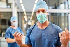 Kirurg med sakkunskap i blåa kirurgiska kläder fotografering för bildbyråer