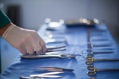 Kirurg som rymmer det kirurgiska hjälpmedlet i operationteater Arkivbilder