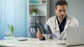 Kirurg som studerar röntgenstrålen av benet och gör receptet i online-kort på bärbara datorn royaltyfri bild