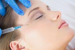 Kirurgdanandeinjektion på galandefot på lugna ligga för kvinna Arkivfoto