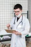 Kirurgdoktor med minnestavladatoren i sjukhuskontor Medicinsk sjukvårdpersonal- och doktorsservice arkivbild