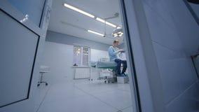Kirurgen undersöker patienten i ett modernt fungeringsrum stock video
