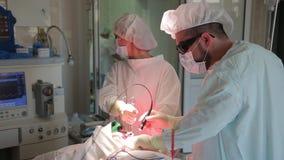 Kirurgen utför ett kirurgiskt tillvägagångssätt Photodynamic terapi en bot för cancer lager videofilmer
