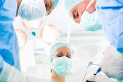 Kirurger som fungerar i rum för operationteater arkivfoton