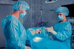 Kirurger team arbete med övervakning av patienten i kirurgisk ope Arkivbilder