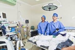Kirurgirum med kirurgen och sjuksköterskor arkivfoto
