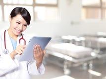 Kirurgkvinnadoktor som använder tabletPCen Arkivfoton