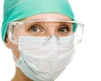 Kirurgkvinnan i skyddande exponeringsglas och maskerar Royaltyfri Foto