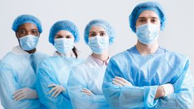 Kirurglag Doktorer som bär den skyddande likformign, ser kameran arkivfoton