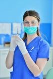Kirurgtandläkaren i maskeringsinnehavinjektionssprutan för att injicera anestesi Arkivfoto