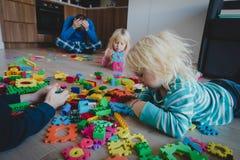 Kis играет дома с игрушками разбросанными повсюду и уставшим вымотанным отцом стоковое фото rf