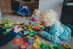 Kis play at home with toys scattered all over and tired exhausted father royalty free stock photo