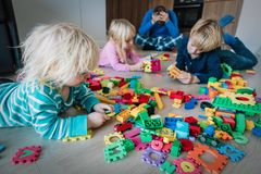 Kis play at home with toys scattered all over and tired exhausted father stock photography