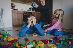 Kis play with toys scattered all over and tired exhausted father. Difficult parenting stock image