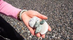 Kiselsten på den kvinnliga handen Arkivbilder
