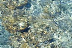 Kiselstenar för havsvatten och vaggar på stranden med ren blå genomskinlig vattenbakgrund Arkivbild