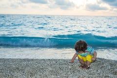 Kiselstenar för litet barnpojke mot efterkrav på havet Royaltyfri Bild