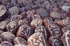 Kiselstenar från den sakrala sjön Manasarovar med hieroglyf och huvudsaklig buddistisk ` för mantra`-Om Mani Padme Hum, arkivbild
