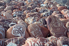 Kiselstenar från den sakrala sjön Manasarovar med hieroglyf och huvudsaklig buddistisk ` för mantra`-Om Mani Padme Hum, Arkivfoto