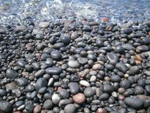 Kiselstenar från den svarta stranden av Santorini Royaltyfria Bilder