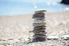 Kiselstenar, i att balansera på stranden Royaltyfri Fotografi