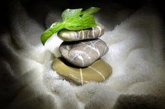 Kiselstenar och murgrönasidor på handduken Arkivfoton