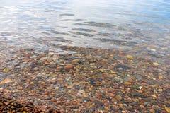 Kiselstenar och små stenar på havsbottnen i ett genomskinligt och en clea royaltyfria bilder