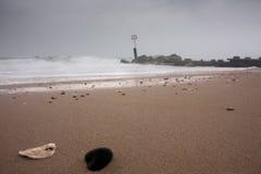 Kiselstenar på den molniga och blåsiga stranden Arkivbilder