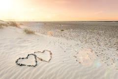 Kiselstenar som är ordnade i form av två hjärtor på sandstranden, skvalpar med härlig solnedgång Royaltyfria Foton