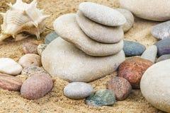 Kiselstenar som staplas på sand Fotografering för Bildbyråer
