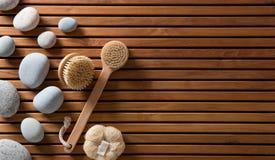 Kiselstenar ställde in på träbräde för turkiskt bad med kroppborstar Arkivfoton