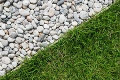 Kiselstensten och grönt gräs Royaltyfria Bilder