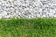 Kiselstensten och grönt gräs Arkivfoton