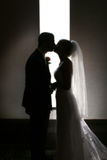 Kiss. A silhouette of a bride and groom kissing in front of a narrow window Stock Photo